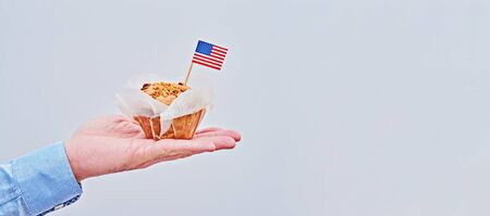 Cupcake with American flag on male palm against light background with copy space. Long banner to Presidents Day, Labor Day, Independence, Flag, Veteran Day, Vote Stock fotó