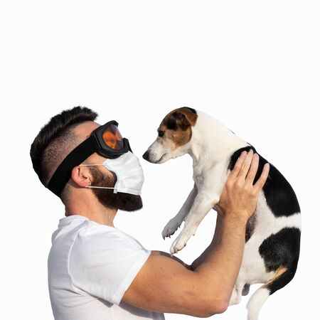 Caucasian bearded man in face mask and protective glasses holding up cute dog jack russell near face. Concept of pet allergy or dog smell in house,isolated on white Stock fotó