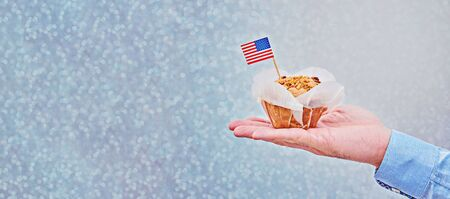 Cupcake with American flag on male palm against blue glitter background with colorful bokeh. Long banner with copy space Presidents Day, Labor Day, Independence, Flag day, Veteran Day, Vote Stock fotó