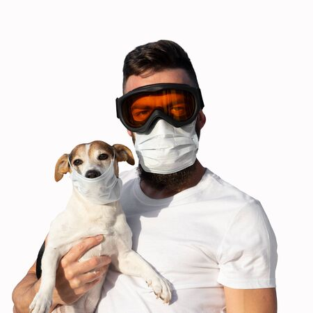 Man in protective mask and glasses holds cute jack russell dog in medical mask. Concept of pet allergy or prevention of viral diseases and coronavirus pandemic, looking at camera, isolated on white