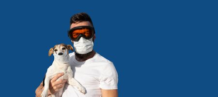 Man in protective mask and glasses holds cute jack russell dog in medical mask. Concept of pet allergy or prevention of viral diseases and coronavirus pandemic, looking at camera, long banner