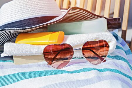 Closeuo of sunscreen cream cosmetic bottles, sunglasses and summer hat on deck chair. Accessories for sunbathing skin during sunbathing Stock fotó