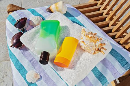 Top view of sunscreen cosmetic bottles and sunglasses in towel on deck chair. Accessories for sunbathing skin during sunbathing