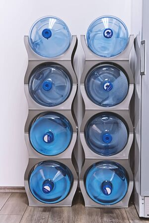 Special shelf for storing plastic gallons of water for dispenser an office area or home. Blue water gallon on electric water cooler