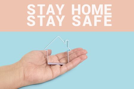 Inscription STAY SAFE and STAY HOME with house in hand palm on blue background. Motivation banner for self-isolation during coronavirus pandemic covid-19