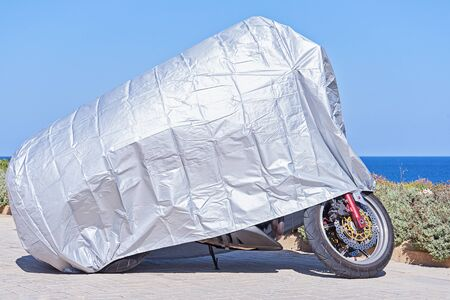 Waterproof cover for motorcycle with silver reflective protective surface. Motorbike covered with fabric shield parked at outdoor Imagens