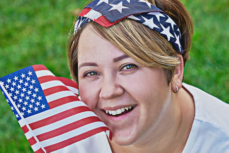 Portrait of smiling caucasian woman in bandana with an American flag during celebration 4th July Independence day
