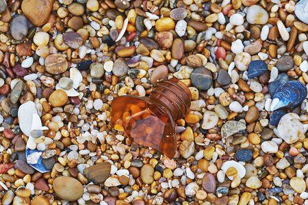 Closeup view of broken bottle at pebble beach. Plastic ocean pollution concept