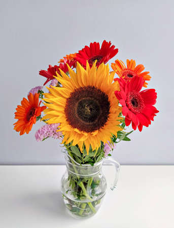 Rustic bouquet with gerbera and single sunflower flower in glass vase against light background