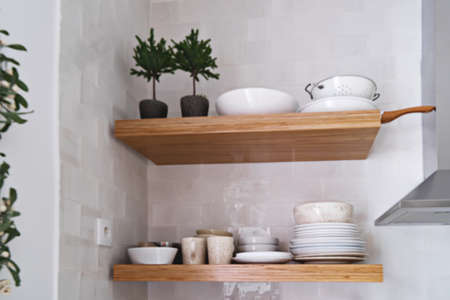 Blurred wooden kitchen shelves with tableware on white brick tile wall in Scandinavian style