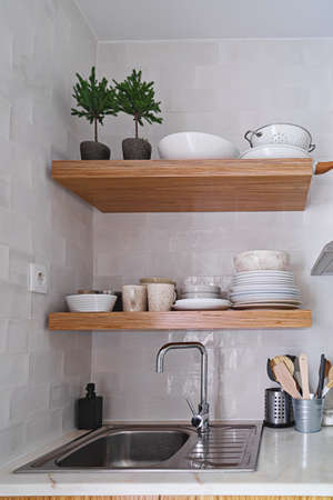 Wooden kitchen shelves with tableware on white brick tile wall in Scandinavian style