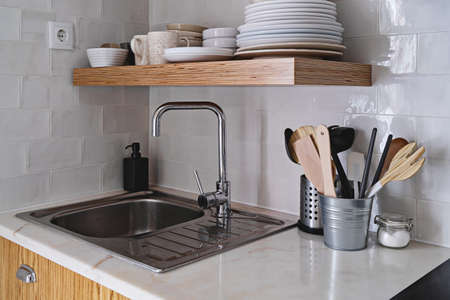 Modern kitchen interior with white brick tile wall in Scandinavian style, wooden shelf, sink and tableware Stock fotó