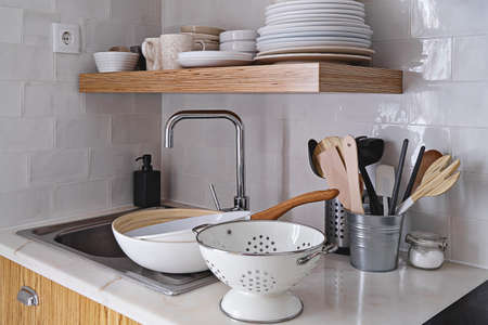 Modern kitchen interior with white brick tile wall in Scandinavian style, wooden shelf, and tableware