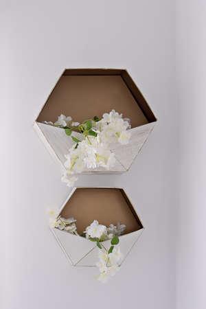 Hexagonal decorative flower storage shelf on white wall. Wedding decor