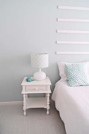 Light green bedroom interior: bedside table and lamp, vertical