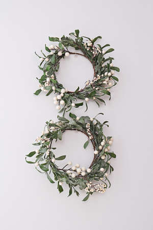 Two decorative mistletoe wreaths hanging on white wall. Home decor in Celtic Christmas tradition