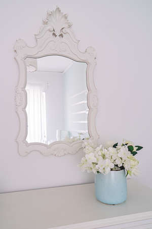 Mirror in carved wooden frame and vase with flowers in bright bedroom interior Banco de Imagens