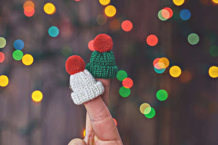 Two faceless romantic couple fingers in knitted hats over Christmas lights background 스톡 콘텐츠