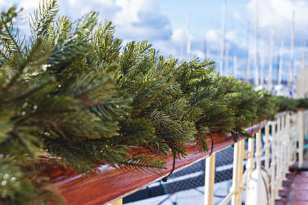 Wooden handrail decorated with fir garland and Christmas lights. Outdoor decor during Christmas Time
