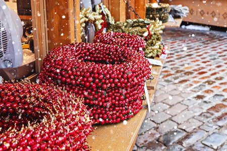 Artificial decorative wreath with red berries on counter during traditional Christmas market in Tallinn city street 스톡 콘텐츠