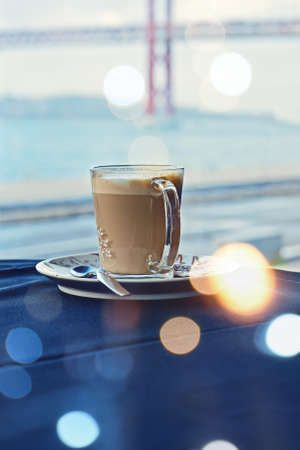 Mug of hot latte on table with blue tablecloth against of window with Lisbon bridge, bokeh