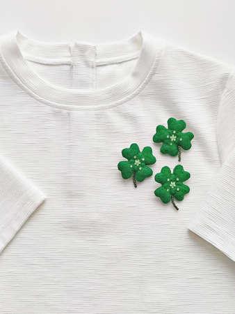 Handmade clover leaf brooch on white T-shirt. Celebrating Saint Patricks Day Concept