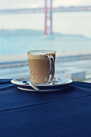 Mug of hot latte on table with blue tablecloth against of window with Lisbon bridge 스톡 콘텐츠