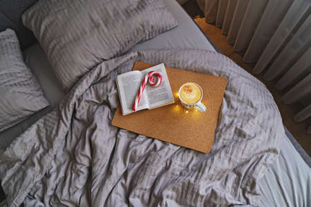 Top view of cozy bedroom with bed in beige colors, coffee mug, peppermint candy cane and book. Lazy Christmas morning in bed