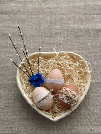 Easter composition decorated by lace Easter eggs in wicker basket on linen background. Plastic-free concept and zero waste