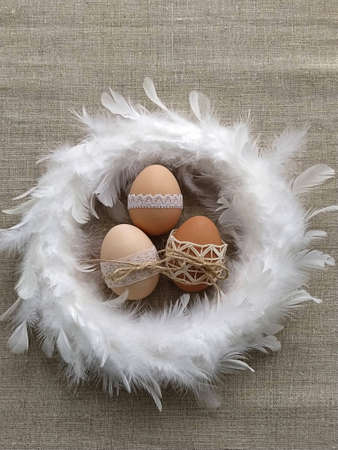 Easter composition decorated by lace Easter eggs in white feather wreath on linen background. Plastic-free concept and zero waste