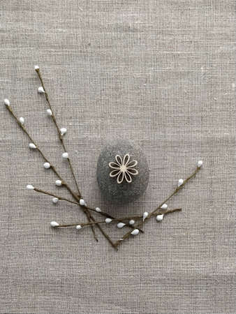 Easter decoration from pebble rock and willow twig on linen cotton background. Plastic-free concept and zero waste