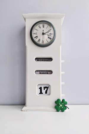 Wooden white vintage clock with calendar and Saint Patricks day cloverleaf on grey background