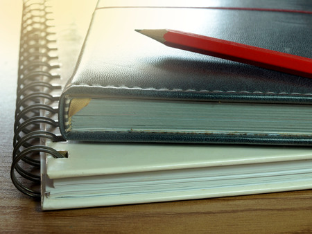 stack of papers: Notebooks with red pencil on wooden table.Shallow depth of field.