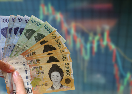 Korean money on display of stock market chart. Financial investment economy concept.