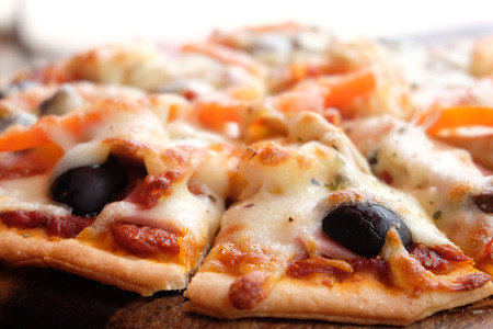 Close up pizza with ham, cheese, tomatoes and olives