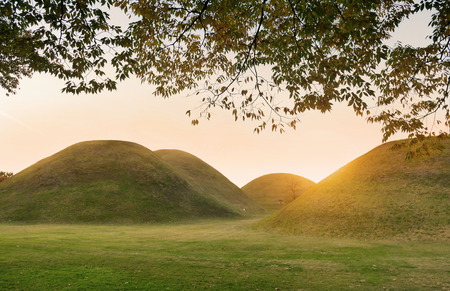 The sunset lights over the Tumuli park royal tombs complex located in Gyeongju, South Korea.