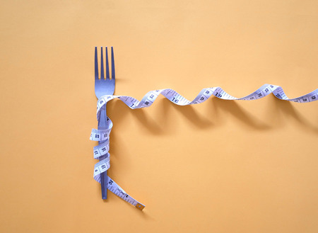 Diet and weight control concept. Measuring tape wrapped around fork lying on yellow background.