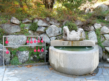 Holy spring water with dipper for drink at Seokguram Grotto Temple Gyeongju, South Korea. Editorial