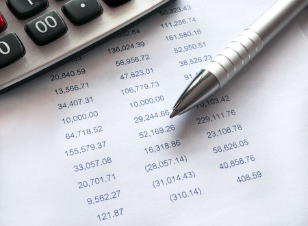 Financial spreadsheet data with pen and calculator.Accounting financial concept.