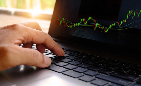 A businessman checking of a stock market graph on a computer screen. Stock fotó