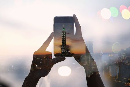 Double exposure of traveler taking picture with a smartphone and cityscape of Taipei 101 building, Taiwan. 版權商用圖片