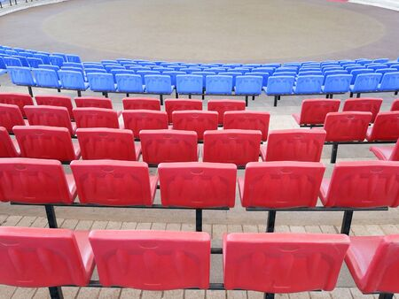 Rows of red and blue seats at indoor amphitheater for local community performances.