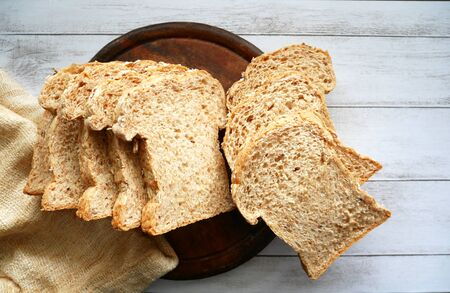 Sliced whole grain bread on wood plate white background. Healthy eating bakery concept.