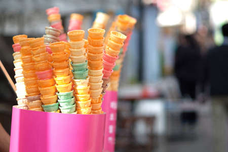 Colorful ice cream cones placed on stalls at outdoor street food market.