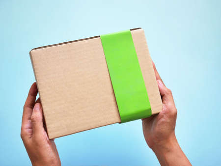 Delivery man holding cardboard box. Online shopping and Express delivery. Standard-Bild