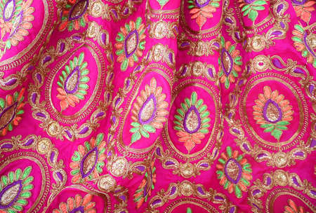 Colorful indian textile fabric embroidery texture background.