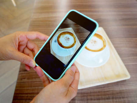 Hand holding smartphone and taking photo of hot cappuccino coffee on wooden table. Standard-Bild