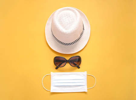 Protective medical mask with hat and sunglasses on yellow background coronavirus covid-19 travel concept.