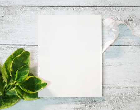 Blank greeting card mockup on old white wooden background.