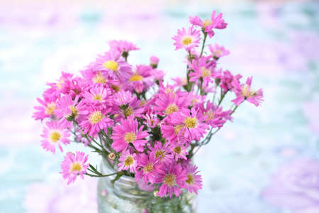 Bouquet of pink flowers in glass vase with blurry natural background.